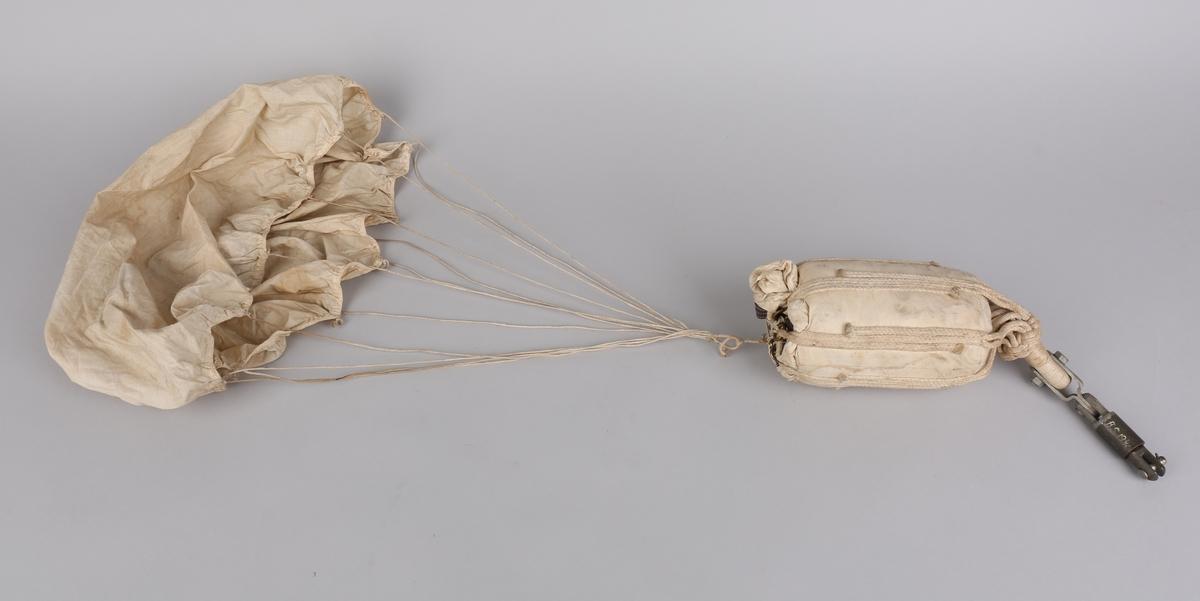 Fallskjerm sammenrullet i liten pose samt en løs reservefallskjerm. Del av luftvernskyts fra krigen 1939-45.
