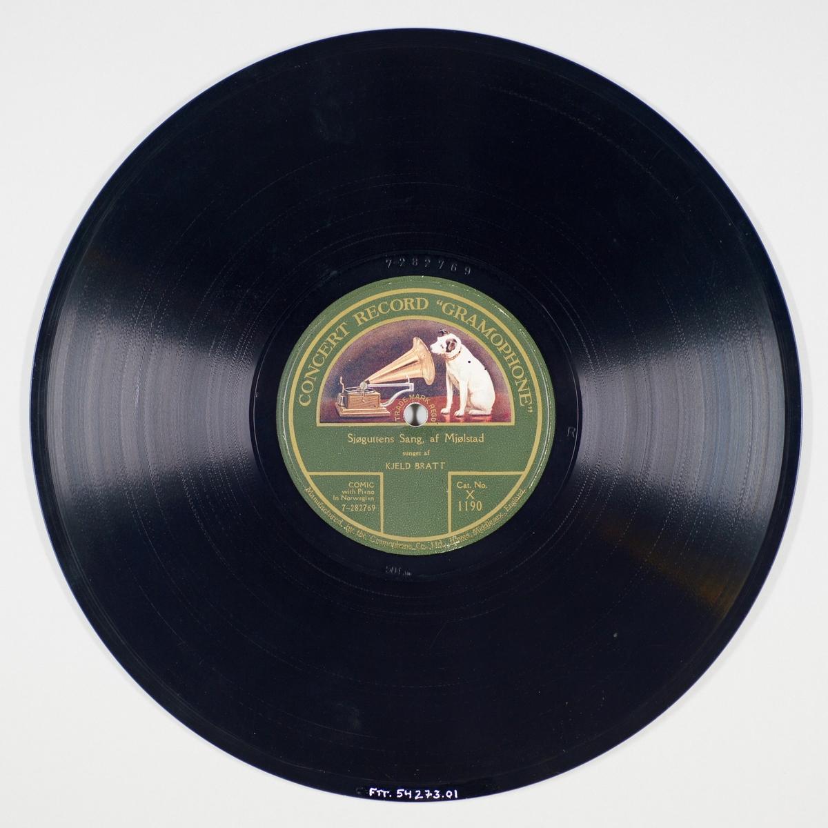 """54273.01: Svart grammofonplate laget av bakelitt og skjellak. Etiketten er grønn med skrift i gull, for tekst se """"Påført tekst/merker"""". På etiketten er det en hund som sitter og lytter til en grammofon. Trykket er i hvitt, grått og ulike nyanser av brunt.   54273.02: Plateomslaget til platen er laget av brunt papir som er limt. For tekst se """"Påført tekst/merker"""". Omslaget har nok opprinnelig tilhørt FTT.54265."""