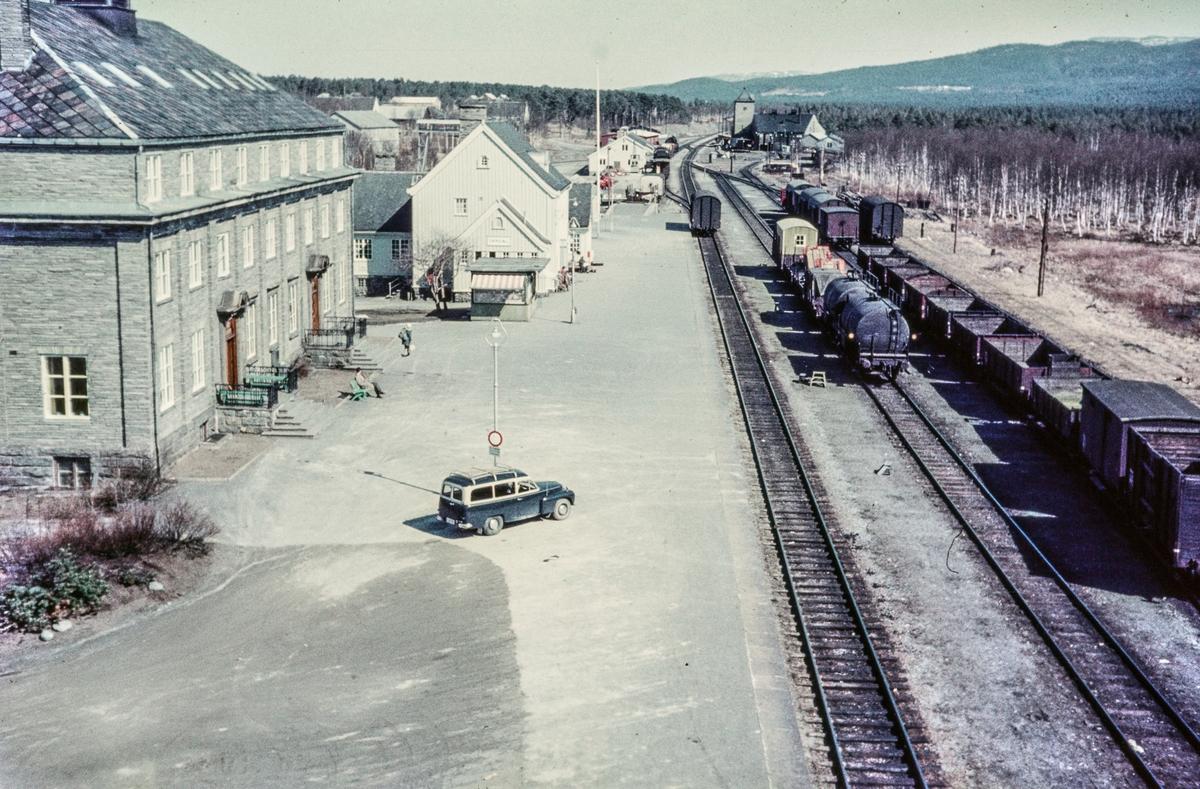 Oversiktsbilde fra Oppdal stasjon på Dovrebanen. Nærmest til venstre Oppdal Turisthotell, bak Oppdal stasjon. Et godstog skifter foran pakkhuset (bakerst til venstre). Bak til høyre sees lokomotivstall og svingskive.