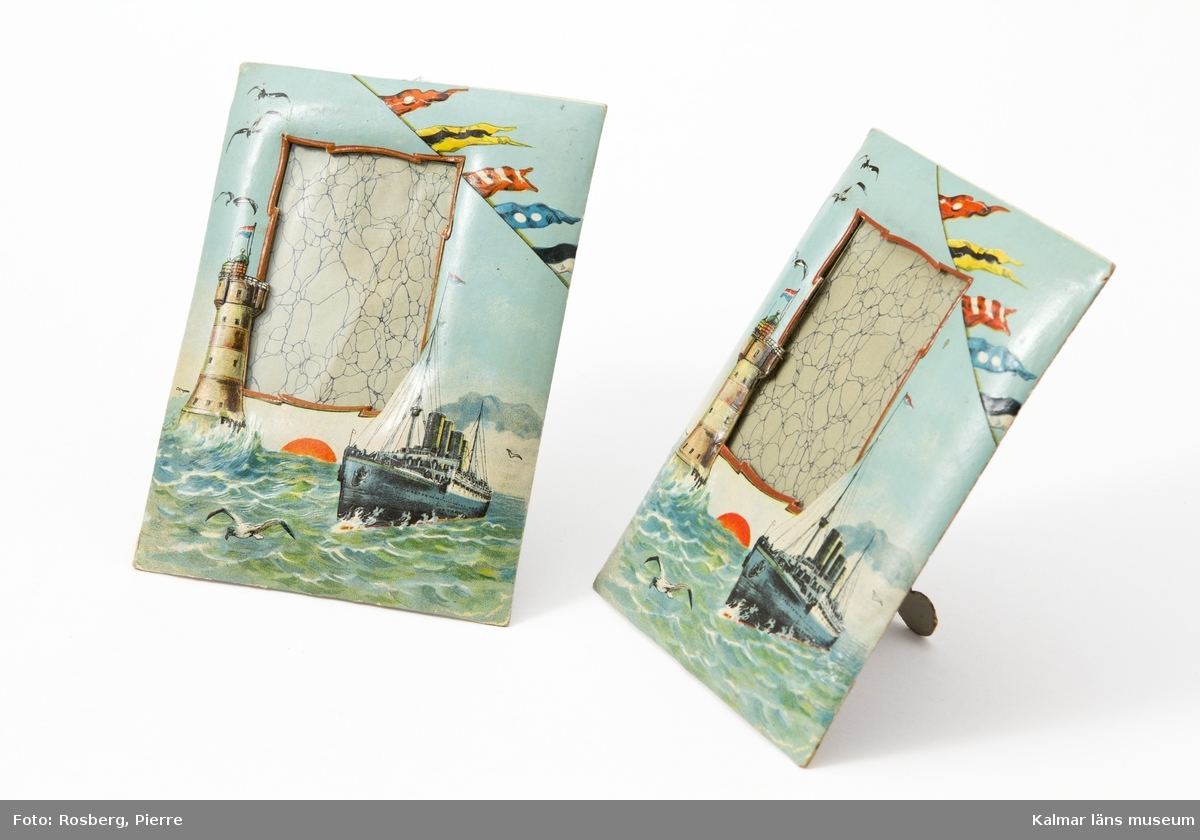 KLM 23031:1-2 Fotoram, två stycken. Sjömansminne. Pressat papper med tryck i färg: fyrtorn, ångare, fiskmåsar och  flaggspel. Endast glasskiva vid platsen för foto.