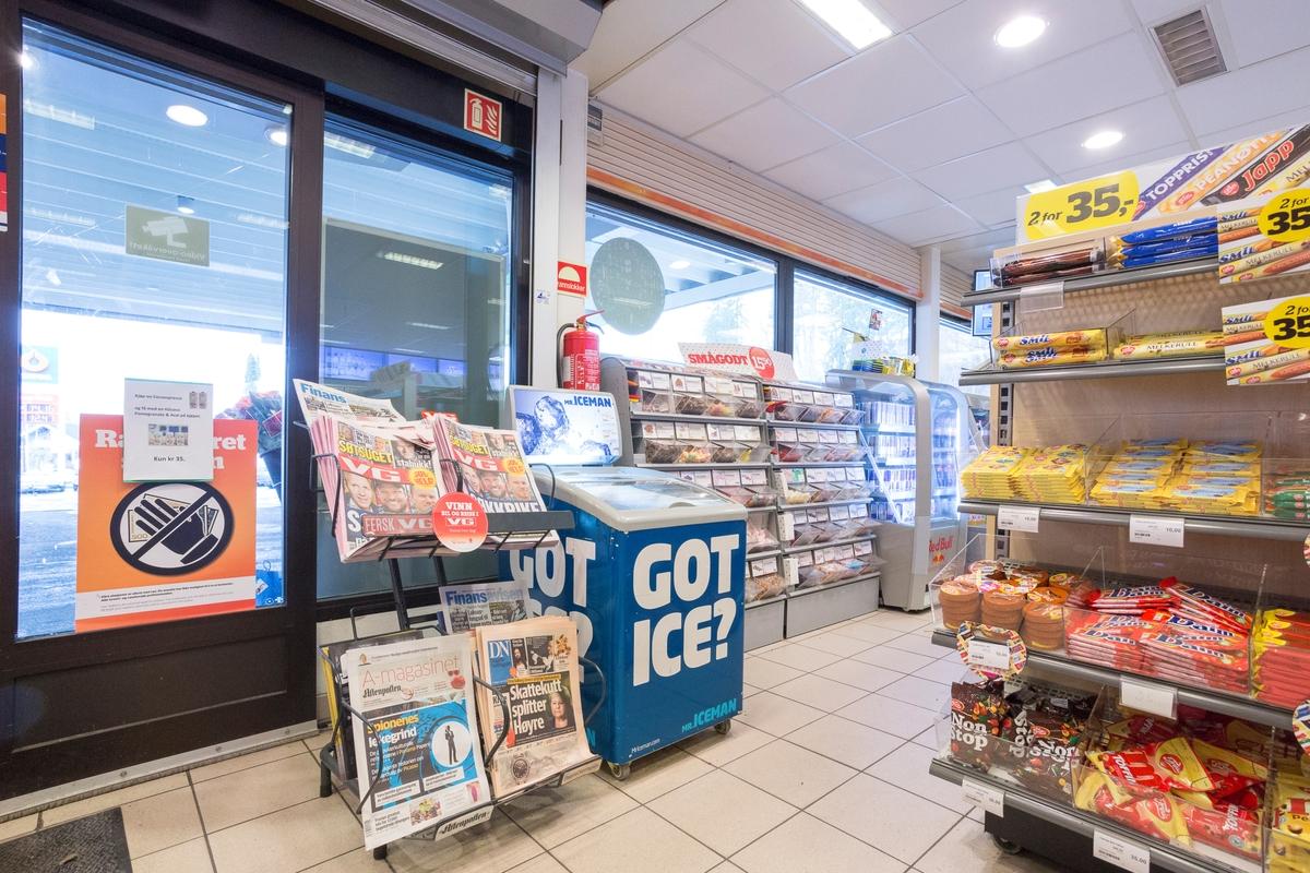Statoil Nadderud. Butikk interiør med fryseboks og stativ med aviser. Hylleseksjon med sjokolader.