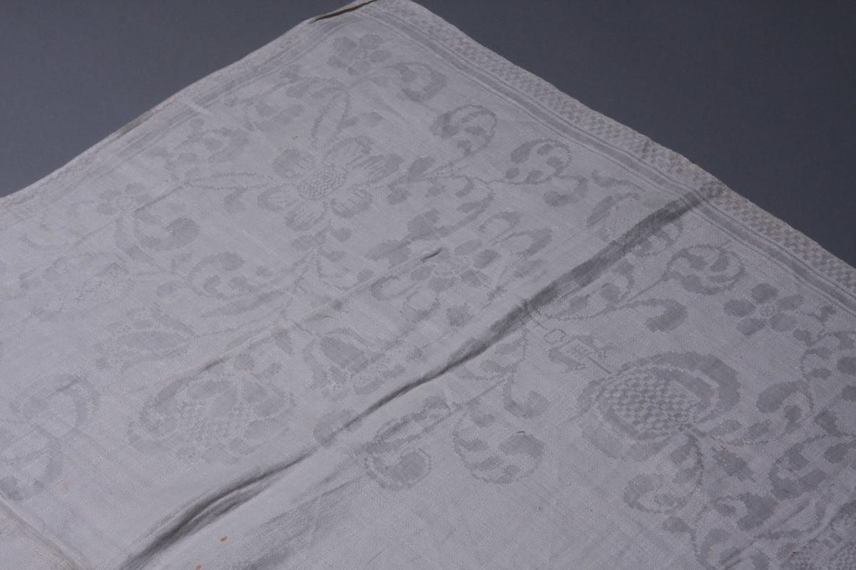 Hvit lindamask med smal sjakkbrett-bord langs sidene. Stort blomstermønster, stiliserte tulipaner fra skjoldformet oppsats med skrårute-mønster. Blomsterbord omkring med hjørnene utfylt. Bekronet monogram (regence) med: BM, speilvendt, sydd med tykksøm.