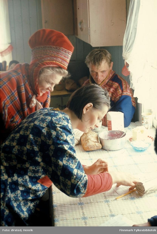 """Postfører Mathis Mathisen Buljo, bedre kjent som """"Post-Mathis"""" i samiske kretser, har kommet frem til en av sine postkunder på ruta for å levere og hente post og andre nyheter. Her står kundene over postpapirer på kjøkkenbordet. Brød og kanskje tyttebær står i bakgrunnen.   Fotograf Henrik Ørsteds bilder er tatt langs den 30 mil lange postruta som strakk seg fra Mieronjavre poståpneri til Náhpolsáiva, videre til Bavtajohka, innover til øvre Anárjohka nasjonalpark som grenser til Finland – og ruta dekket nærmere 30 reindriftsenheter. Ørsted fulgte «Post-Mathis», Mathis Mathisen Buljo som dekket et imponerende område med omtrent 30.000 dyr og reingjetere som stadig var ute i terrenget og i forflytning. Dette var landets lengste postrute og postlevering under krevende vær- og føreforhold var beregnet til 2 dager. Bildene gir et unikt innblikk i samisk reindriftskultur på 1970-tallet. Fotograf Henrik Ørsted har donert ca. 1800 negativer og lysbilder til Finnmark Fylkesbibliotek i 2010."""