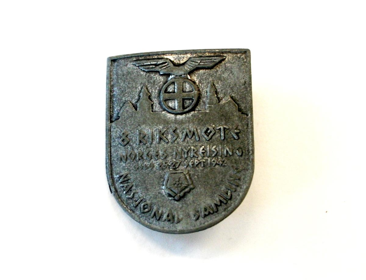 NS-emblem (solkors under ørn) med siluett av hus på begge sider. Mot bunnen av merket er det også et femkantet symbol med en rosett i midten.