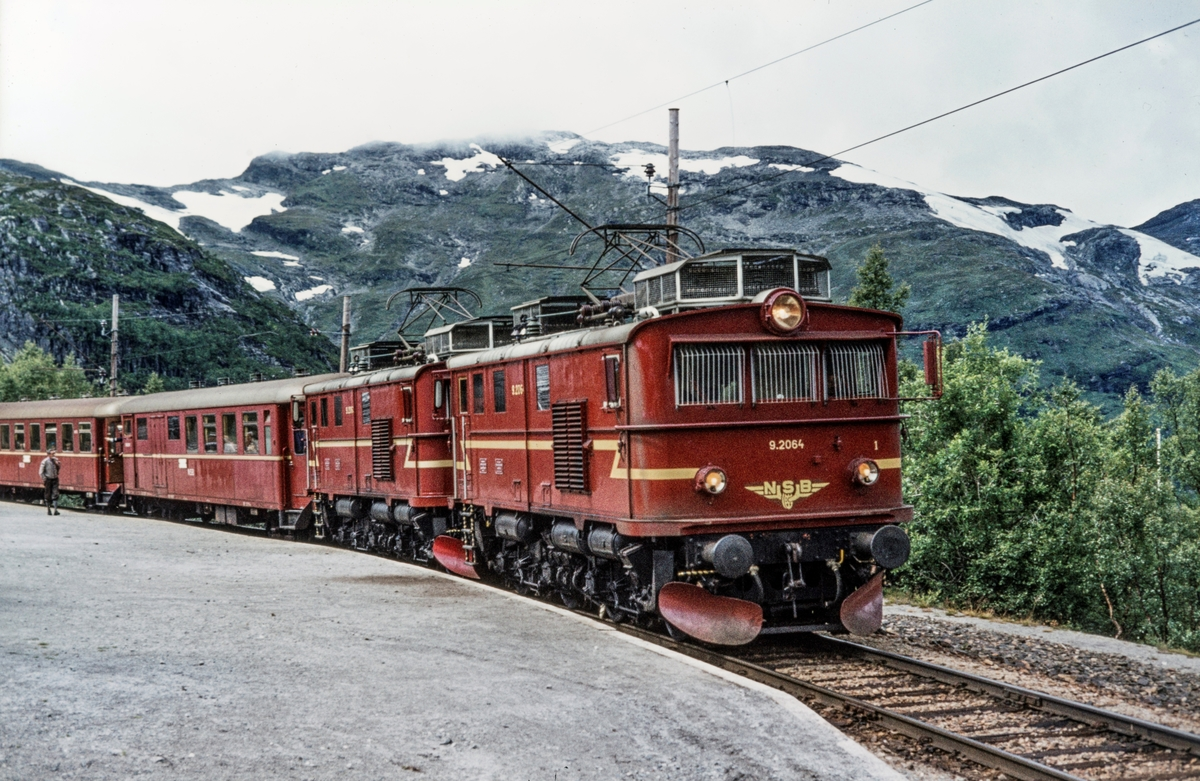 Persontog fra Myrdal til Flåm på Vatnahalsen holdeplass. Toget trekkes av elektriske lokomotiver type El 9 nr. 2064 og 2063.