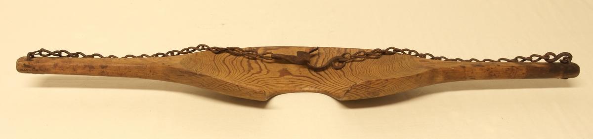 Åk i skåret og pusset furu. I hver ende av åket er det festet smidde jernlenker med krok nederst.