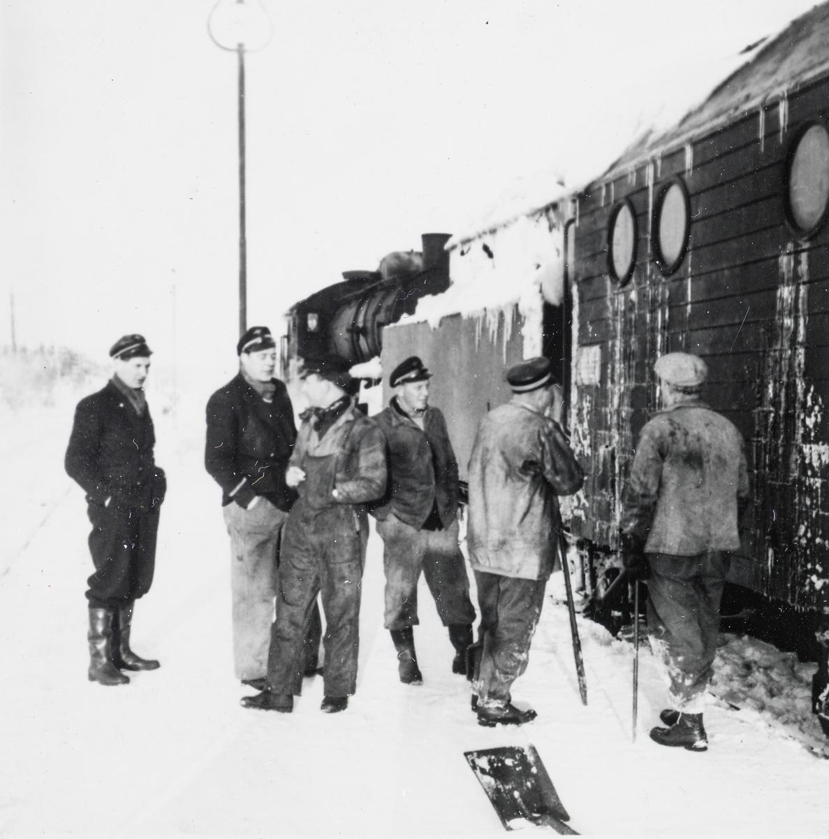 Jernbanepersonale foran snøryddingstog på Nordlandsbanen. Nærmest roterende snøplog type III, bak damplokomotiv type 33c nr. 396.