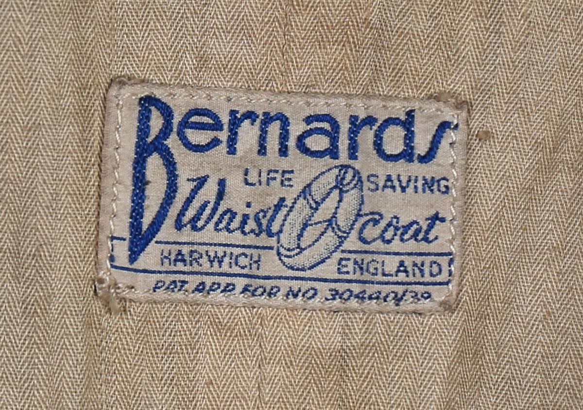 Livvest i sort ullstoff med for. Oppblåsbar ved hjelp av fleksibel slange med munnstykke som er montert i lomme. Trolig produsert på begynnelsen av 1900-tallet.