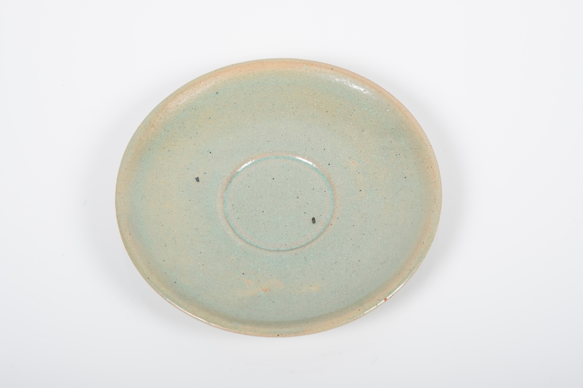 Sskål i keramikk med grønn lasur. Spor etter tre knotter på bunnen, usikker funksjon. Bunnen har matt overflate.