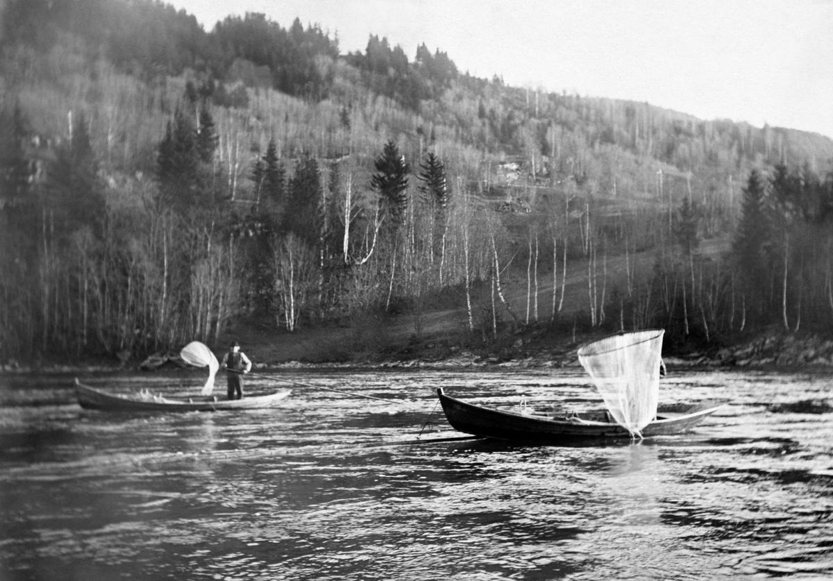 Håvfiske etter lågåsild i den nedre delen av Gudbrandsdalslågen, antakelig ved den lokaliteten som kalles Bottomsrevet, tidlig på 1900-tallet.  Dette fisket ble særlig drevet i et elveparti der det var for strid strøm og for steinete til at det var hensiktsmessig å fiske med not eller garn.  Bildet viser to båter – såkalte «åfløyer» - som lå fastbundet til stokker som fiskerne hadde festet i elvefaret med henblikk på dette fisket.  Fiskerne førte håvene ned i vatnet så langt opp på motstrøms side de greide, og deretter førte de fangstposene i strømretningen langs båtsidene nedover.  Dette måtte gjøres i en hastighet som var raskere enn elvestrømmens.  Bevegelsen videreføres inntil fiskerne når den nedre enden av båten, og håvstanga («rauna») ikke når lenger.  Da heves håven, og hvis «påså'n» inneholdt fisk, ble den tømt i båten før neste drag langs elvebotnen.  Suksessen var avhengig av hvor tette stimende av gytende lågåsild ved fiskeplassen var.  Stokkhåvfisket foregikk helst nattestid.  På dette bildet ser vi to fiskere som hadde fortøyd båtene sine i hver sin stokk, ikke langt fra hverandre, for å drive håvfiske i det samme elvepartiet.  Fotografiet er brukt som illustrasjon i fotografen Hartvig Huitfeldt-Kaas' bok «Mjøsens fisker og fiskerier» (1917), side 73.  Huitfeldt-Kaas' beskrivelse av dette fisket er gjengitt under fanen «Opplysninger».