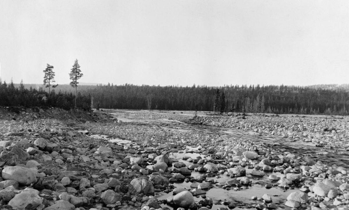 Erodert landskap nedenfor Osfallet, der et dambrudd den 10. mai 1916.  Dambruddet forårsaket at elva grov seg et nytt løp nord for det opprinnelige ved dammen, og strømmen skylte med seg mye av jordsmonnet og vegetasjonen på strekningen mellom dammen og Søndre Osas utløp i Rena.  Dette fotografiet viser konsekvensene av dambruddet i området nedenfor.  Vi ser et forholdsvis flatt landskap, der med et elveløp omgitt av utvaskete arealer med mye overflatestein.  Bildet er tatt fire år etter dambruddet.  På en landtange som ikke ble berørt av dambruddet, til venstre i bildet, skimter vi en husgavl.