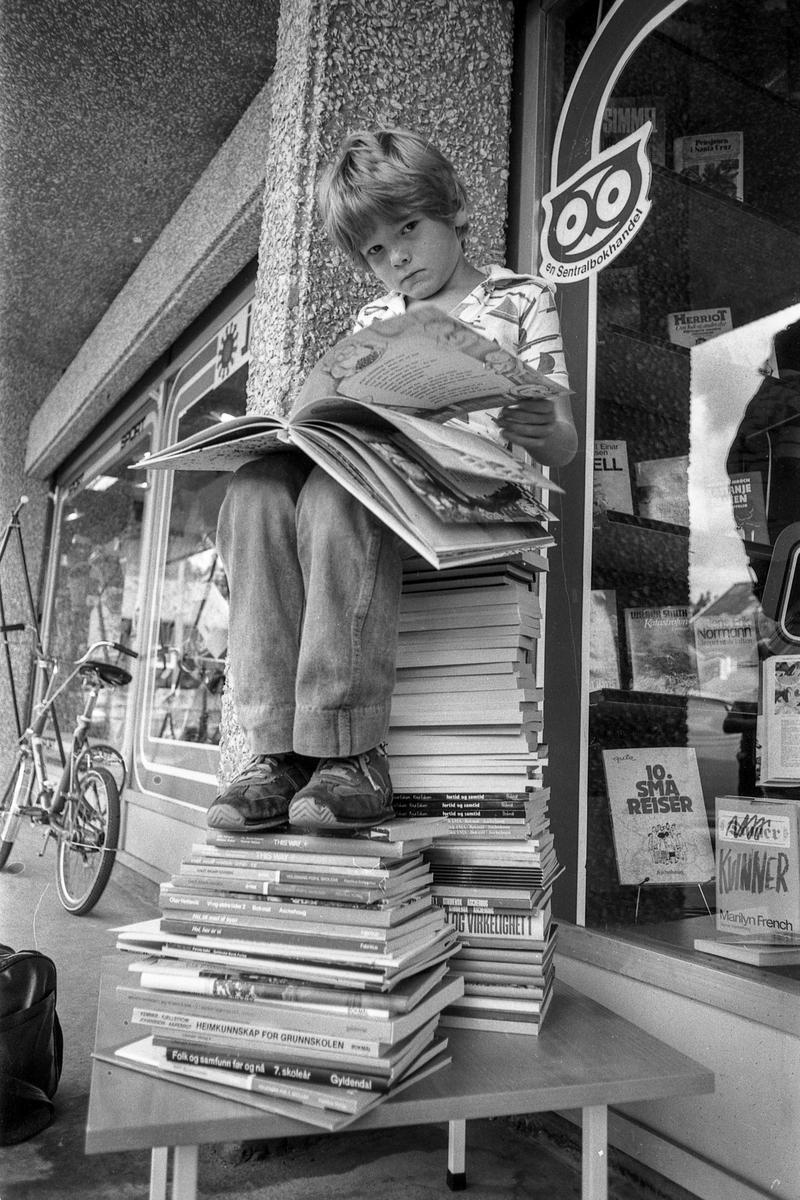 Tanum bøker og papir, Sentrumsbygget på Kolbotn. Gutt på en bokhaug. Sønn av Sverre Strømmen fra Tårnåsen. Fotograf: ØB Ukjent