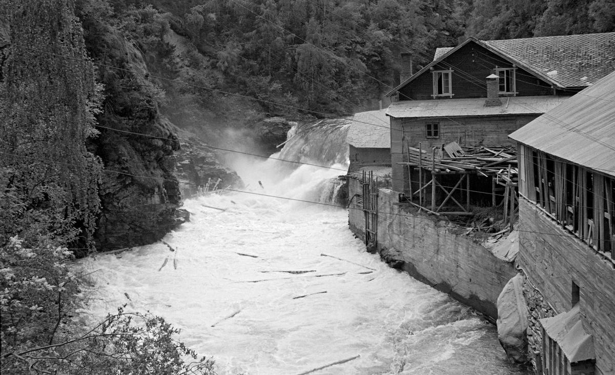 Sag- og møllebruket ved Vinsterfossen i Loholet, i elva Vinstra i Nord-Fron kommune i Oppland fylke. Fotografiet er tatt fra brua nedenfor den nevnte fossen. Loholet er navnet på et trangt gjel der elva renner mellom steile bergskrenter. I dette gjelet ble det i sin tid bygd en dam av tømmer og stedlige stein- og grusmasser, noe som skapte et fall på ni meter. Dette fallet gav energi til de tekniske installasjonene nedenfor fossen. Her lå Vinstra bruk, med både møllebygning og sagbruk.  Da dette fotografiet ble tatt, våren 1950, var det flom i Vinstra, og elva gikk stor over dammen med løstømmer fra skogene ovenfor.  Opprinnelig var det brukerne på gardene Øvre Bryn (på sørsida) og Lo (på nordsida) som disponerte fallrettighetene i Lofossen.  Dette representerte en betydelig verdi, for elva hadde stabil vannføring, slik at fossen kunne gi kraft til oppgangssager og kverner.  Stedet lå dessuten sentralt til, ved ei bru på bygdevegen på vestsida av Gudbrandsdalslågen (Baksida).  I 1870 lot Lodver Lo eiendomsspekulanten Peder Carlsen Foss (Fossgarden) leie fallrettighetene ved Loholet og en tilstøtende skogteig med sikte på å bygge sag- eller møllebruk.  Planen ble realisert, men Peder Carlsen gikk konkurs, og både skogeiendommene i Midtdalen og sagbruket ved Vinstrafossen ble solgt på auksjon i 1890-91.  Sagbruket var det tilsynelatende en advokat som kjøpte på vegne av Gjøvik Dampsag & Høvleri som kjøpte, men de overlot kjøpet til to lokale karer, Ole Simensen Kongsli og Johan Olsen Tårud.  Disse dannet et driftsselskap for «Vinstra bruk», der også Ole J. Teige var med som kompanjong.  I 1910, etter at Sigurd Kongsli hadde overtatt farens rettigheter i bruket, ble det installert en liten elektrisk generator i en av turbinene på bruket, den første i sitt slag i Nord-Fron kommune.  Elektrisk lys var attraktivt, og i 1914 kjøpte Sigurd Kongsli en større turbin med større generator.  Dermed kunne Vinstra Bruk også begynne å selge overskuddskraft til sambygdingene, etter 