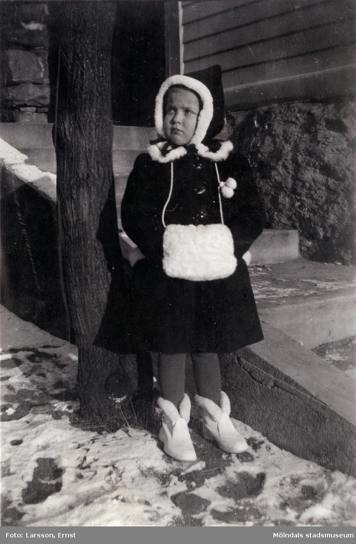 """Berit Gustafsson (född 1936) vinterklädd i muff och kappa en kall vinter i början av 1940-talet. Platsen är i """"Stusshålan"""", Kryssgatan i Mölndal."""