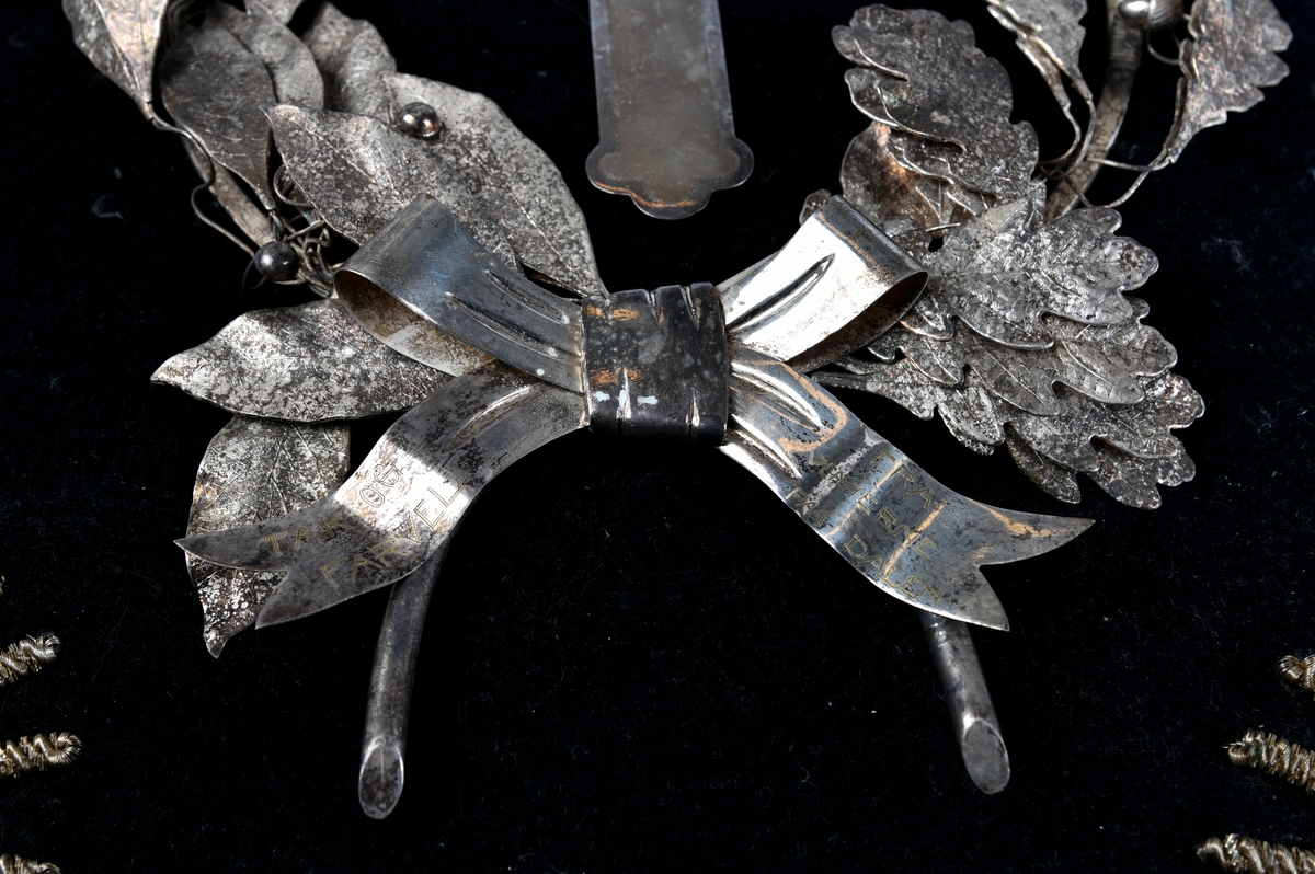 Sølvkrans av laurbær og eikeløv med sløyfe nederst. Mellom de bøyde greinene er det et sølvkors. Kransen er sydd ned på en svart fløyelspute med dusker i hjørnene. Sølvsnor påsydd rundt puta.  Det finnes to like kranser som denne publisert på Digitalt museum. Den ene er udatert, men den andre er også produsert i 1924 - og befinner seg på Mjøsmuseet.