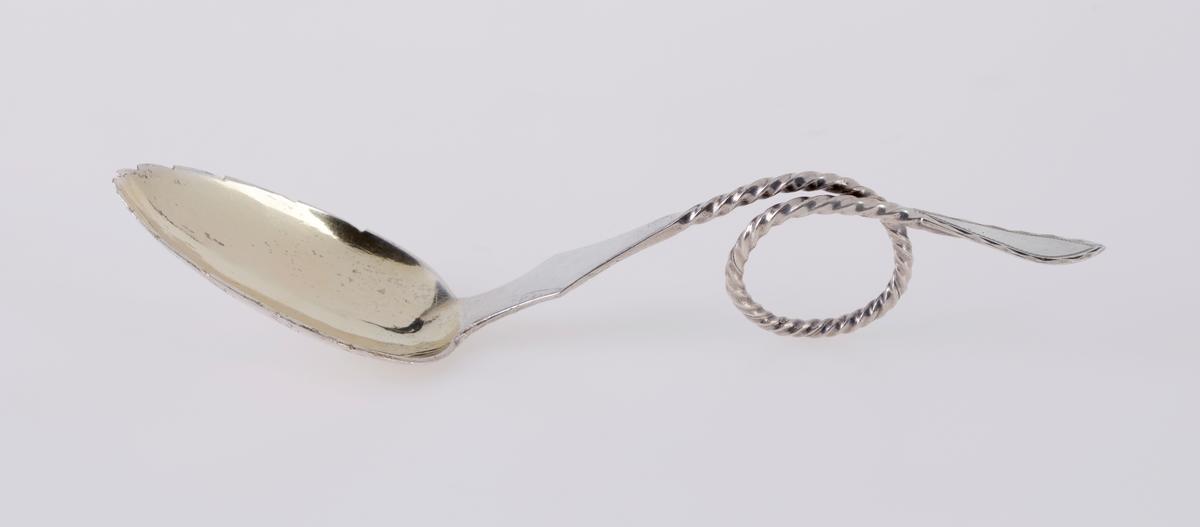 """En sukkerskje av sølv. Bladet har hakk i sidene som minner om et bjørkeblad. På undersiden er det gravert inn """"nerver"""" i bladet. Skaftet er flatt øverst før det er snodd/tvunnet. På midten er det en løkke/sirkel som fungerer som håndtak Øverst på skaftet/håndtaket er det gravert inn mønster langs kanten. På baksiden er det et sølvstempel, se """"Påført tekst/merker""""."""