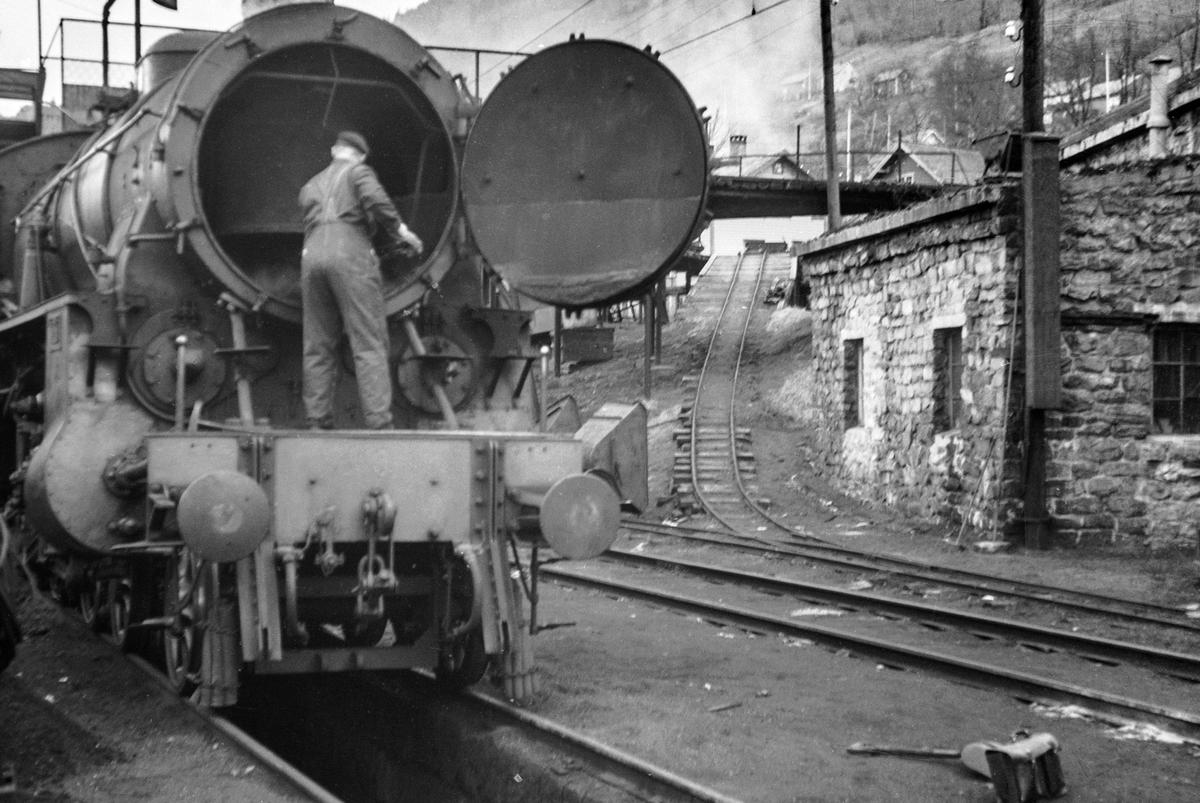 En lokstallbetjent spart ut stubb av forenden på damplokomotiv type 31b nr. 400. Til høyre trallebanen for vagger på kullingsanlegget på Voss stasjon.