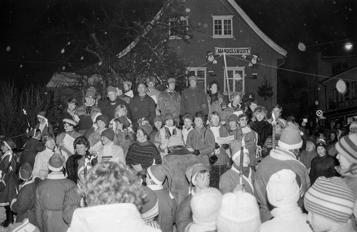 Julegateåpning i Drøbak med langbord, juletre, nisser med fakler og mange mennesker.