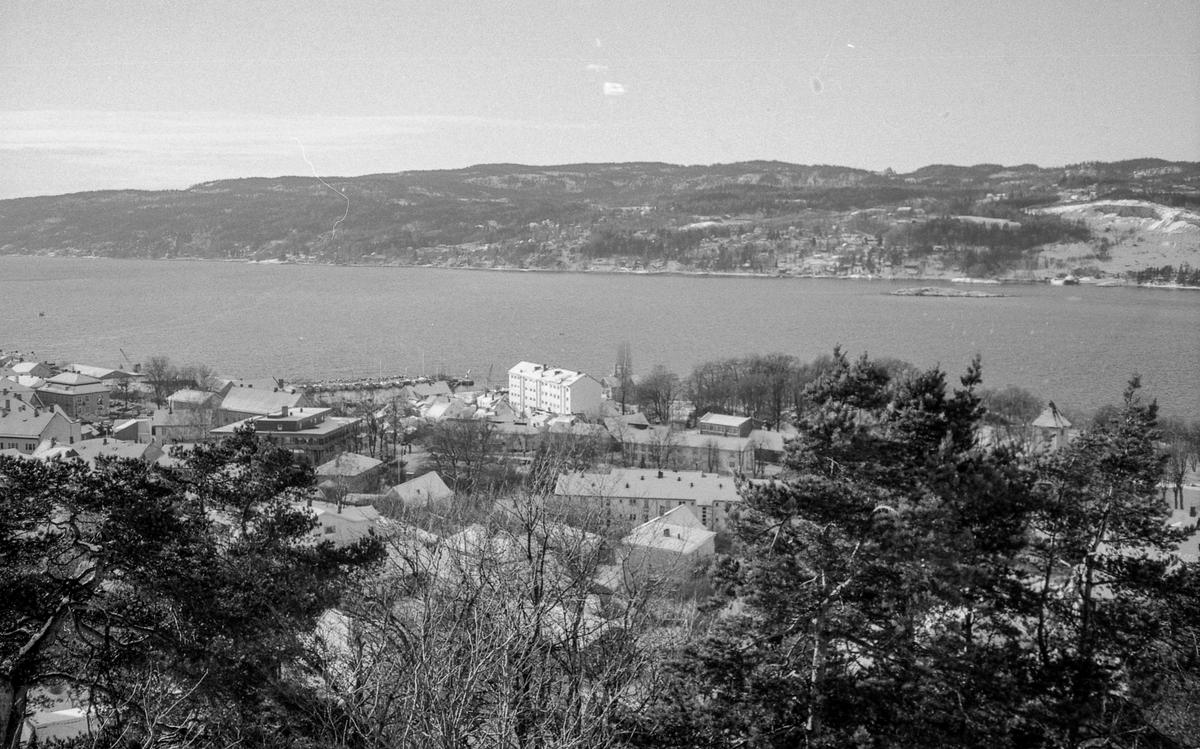 Utsiktsbilde over Frogn og Drøbak over Oslofjorde mot Hurumlandet. Vinterlandslap med småhusbebyggelse og blokker.