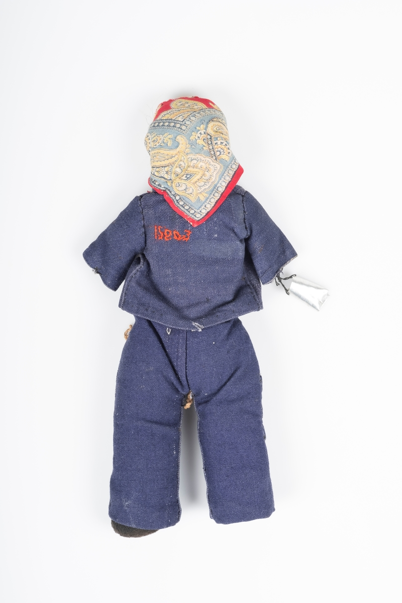 En dukke som forestiller en kvinnelig fange, sydd av bomullsstoff. Kroppen er sydd med paisley-mønstret stoff, og er fylt med bomull eller vatt. Hodet er sydd med beigefarget stoff. Føttene er sydd med svart stoff.   Dukken har på seg en mørk blå fangedrakt bestående av bukse og jakke. Buksen har et flettet belte av brun hyssing. Det er to lommer foran. Jakken har 3 lommer foran og brodert fangenummer (15803) bak.   På hodet har hun på seg en sjal/skaut i paisley-mønstret stoff. Under sjalet/skauten stikker det fram litt hår, som trolig er ekte hår.   Fra armen henger det en liten bøtte av metall.