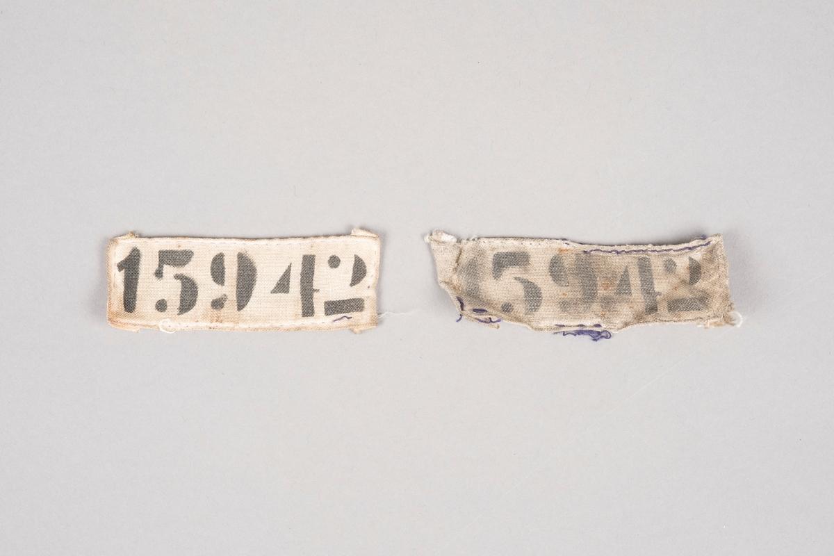 To merkelapper i naturhvitt lerretsstoff med nummeret 15942 trykket på med sort blekk. Den ene merkelappen har søm av mørk blå tråd på kantene. Deler av tråden er raknet.