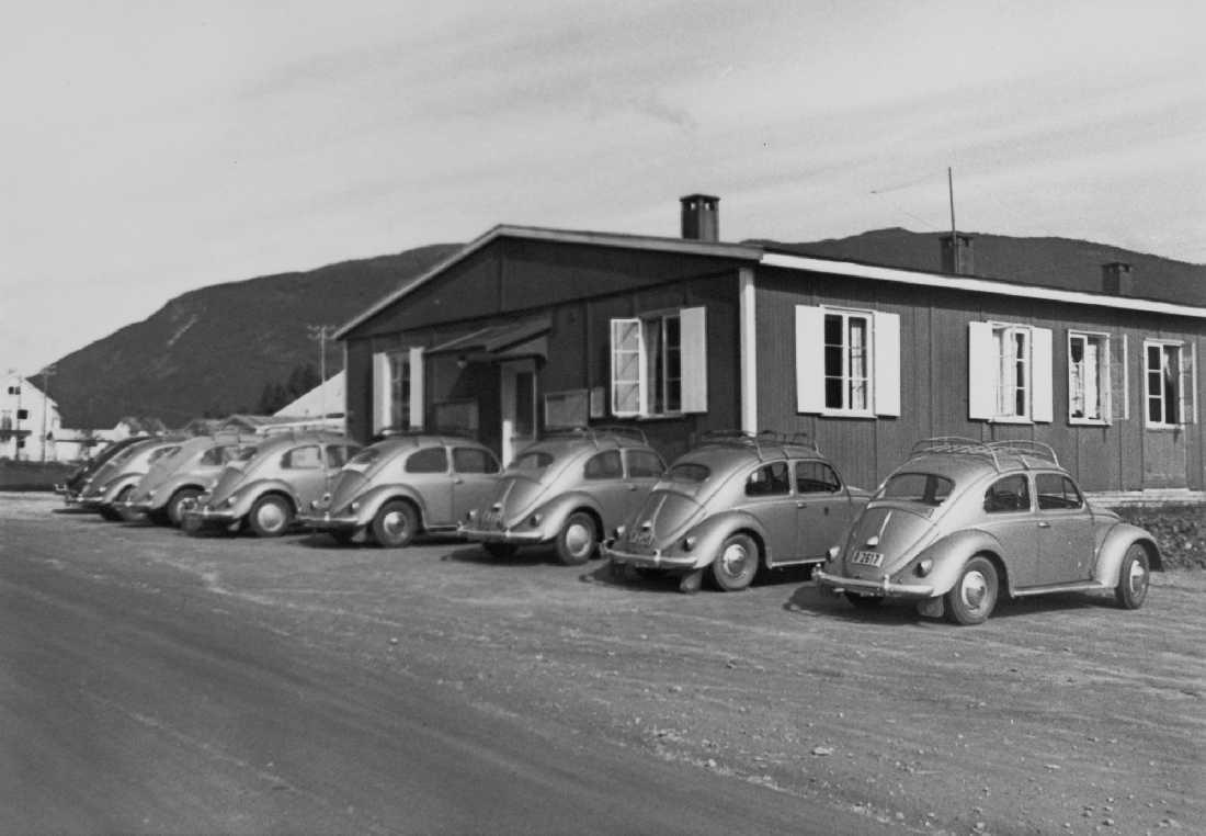 """Opprinnelig arkivnr. 0656. Felles. Kontorbrakken i Korgen. Her holdt anleggsadministrasjonen til i tidsrommet 1949-1963, til den ble flyttet til Selfors. Anleggets 8 stk. nystriglete VW Bobler i """"skryteposisjon"""". Rasjoneringen av personbiler av vestlig fabrikat ble opphevet 1. oktober 1960."""