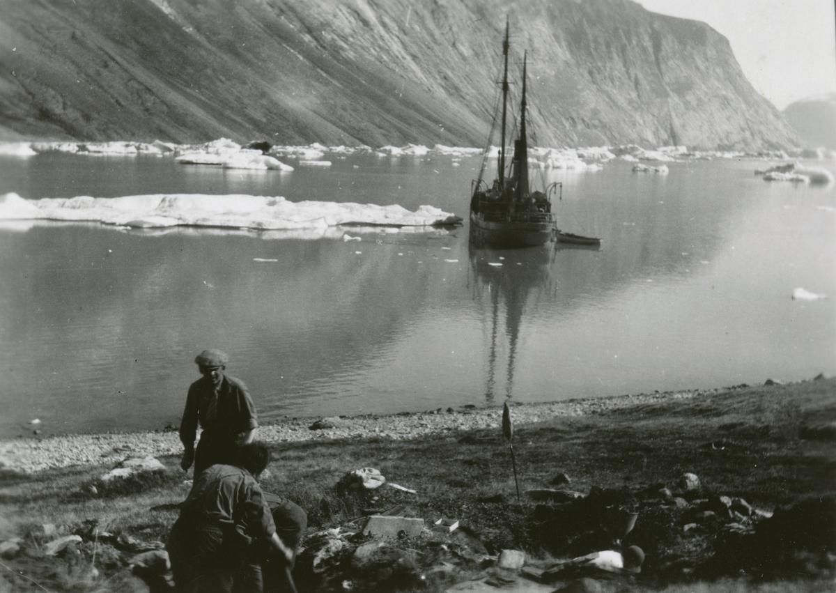 Ingvald Skjeldrup gjør utgravinger av et eskimohus sammen med en annen i Reinbukten, Isfjorden på Grønland. Båten Veslekari viser i bakgrunnen.