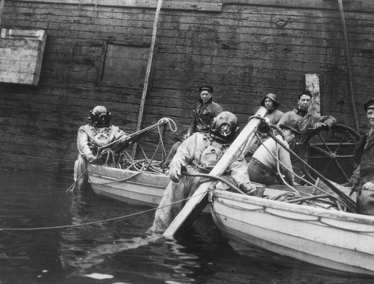To hjelmdykkere og fem arbeidsfolk ombord i to lettbåter. Båtene ligger inntil en skuteside. Hjelmdykkeren med sigarett i munnen er Bernhard Meier Sebak (1894-1976).