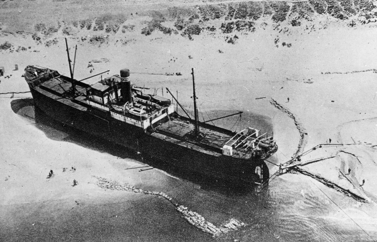 Ukjent havarert motorskip, ligger på land på en sandbank eller sandstrand. Flyfoto.