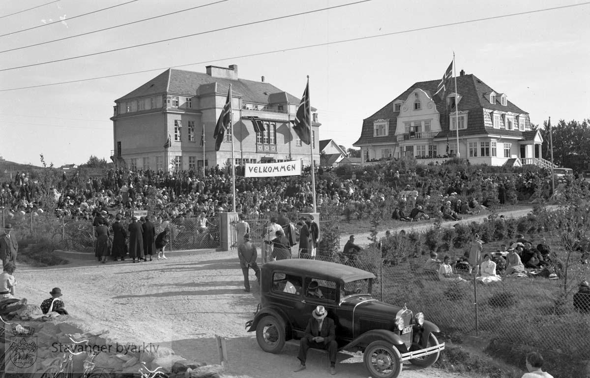 Stor forsamling utenfor Solborg folkehøgskole. En bil parkert i forgrunnen.