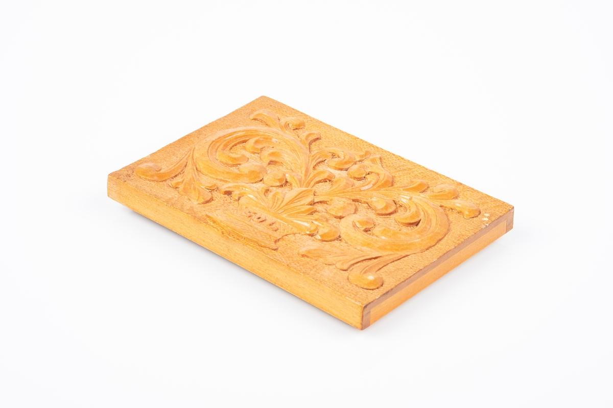 Et lokk til treskin. Lokket har utskåret akantusmønster. På innsiden av lokker er det skrevet en hilsen. Hele lokket er lakkert.