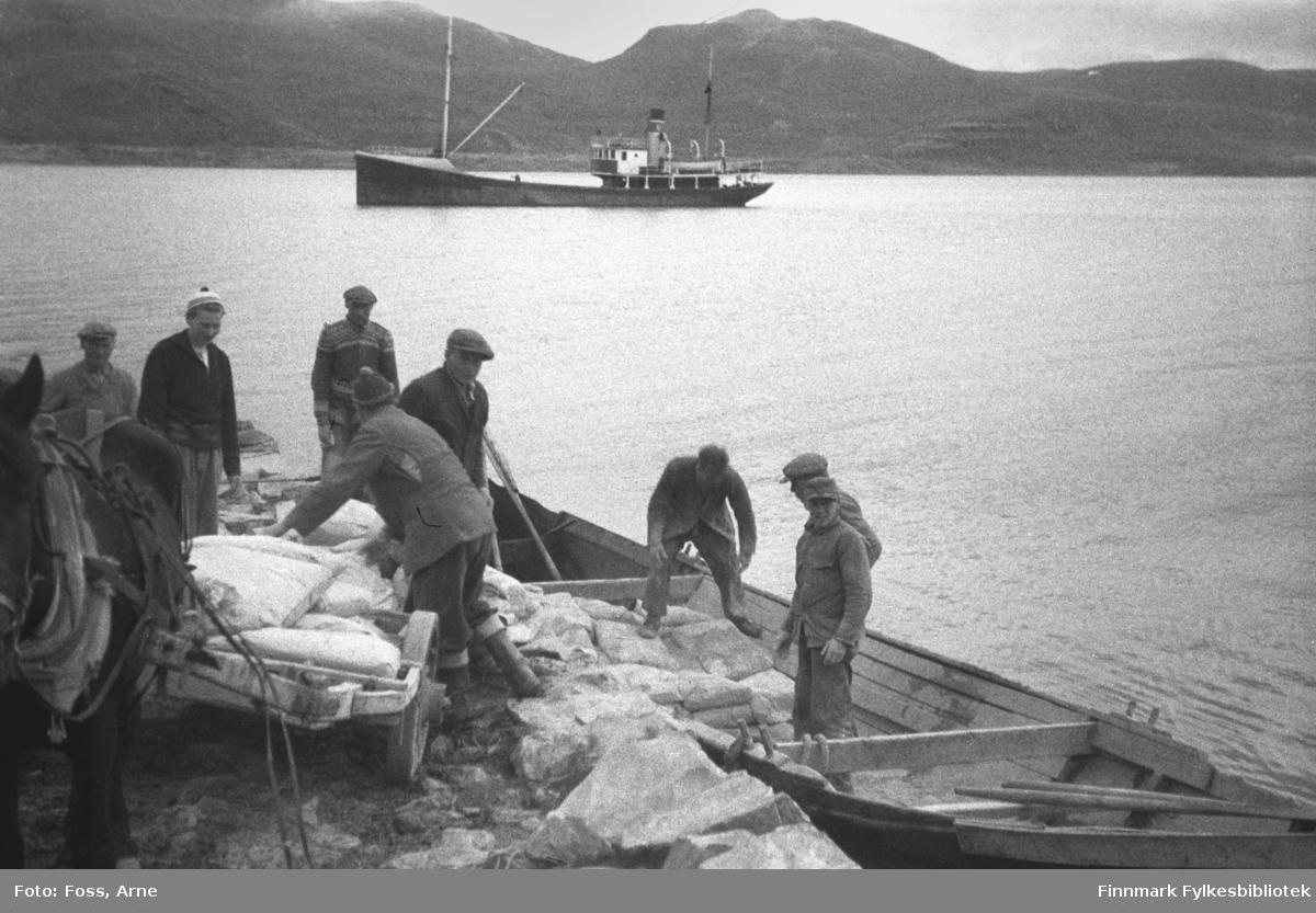 Sekker av sement tas av båten og stables på en hestekjerre. Tidspunkt er juni-juli 1946. Stedet er Smalfjord.