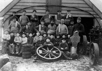 Arbeidere ved Georg og Arent Gjertsens reperbane på Laksevågneset i Bergen. Mennene med bast/hamp om livet og skinn på skuldrene. 14 smågutter  på rad en og to.