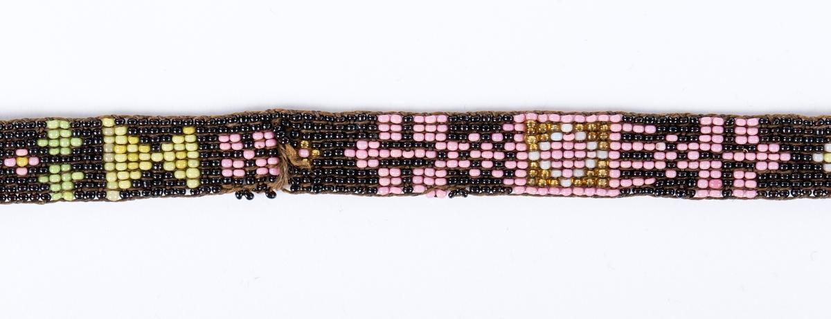 Smalt bånd, ca 1 cm br. Tett perlemønster. Antakelig vevet eller brodert med perletredd tråd. Knyttebånd i brun silke. Slitasjeskader på 8 steder. Merkelapp har antakelig fulgt med ved innlevering til museet, eller ved en utstilling i glassmonter i Børsumbygningen
