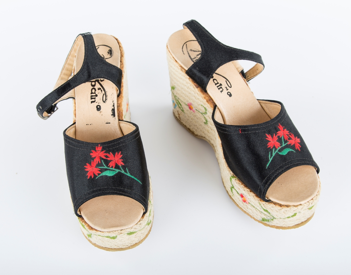 """Platå sko, svart med rød blomst.  """"Platå sko fra 1974, kjøpt i Haftenssund i Sverige under årets sommerferie i seilbåt. En fantastisk sommer, med bare sol. Regn en natt på 4 uker i skjærgården."""" Tidligere eier"""