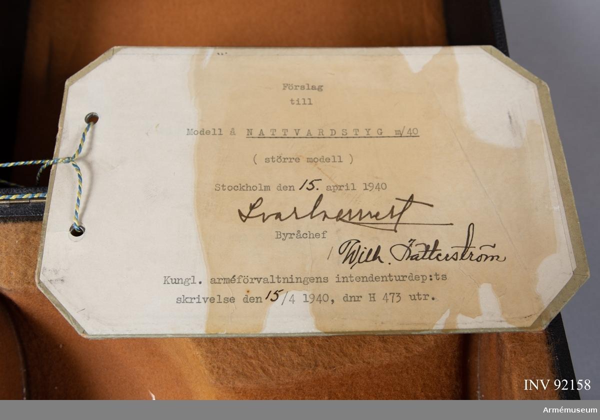 """Modellexemplar av nattvardskalk m/1940, större modell i tenn. Märkt """"N Redeby"""" inuti foten. Förvaras tillsammmans med paten i svart fodral försett med sigill samt etikett signerad av byråchefen för Kungliga arméförvaltningens intendenturdepartement den 15 april 1940."""