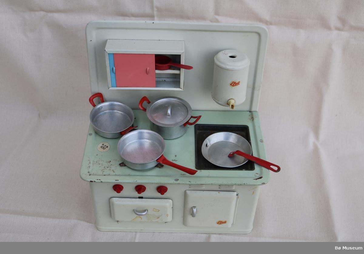 Lite leikekjøkken i fleire delar. Integrert i leikekjøkkenet (a) er det komfyr, steikeomn, vask, varmtvasstank, overskåp, vask og skåp under vasken.  Til dei tri komfyrplatene har hatt kvar sin brenner. Ein brenner manglar. Skåpdørene kan opnast og kummen kan takast ut. Av lause delar som høyrer til er: b - Gryte c - Kjele med lok d - Djup steikepanne e - Steikepanne med laus handtak f - lita raud sil av plast