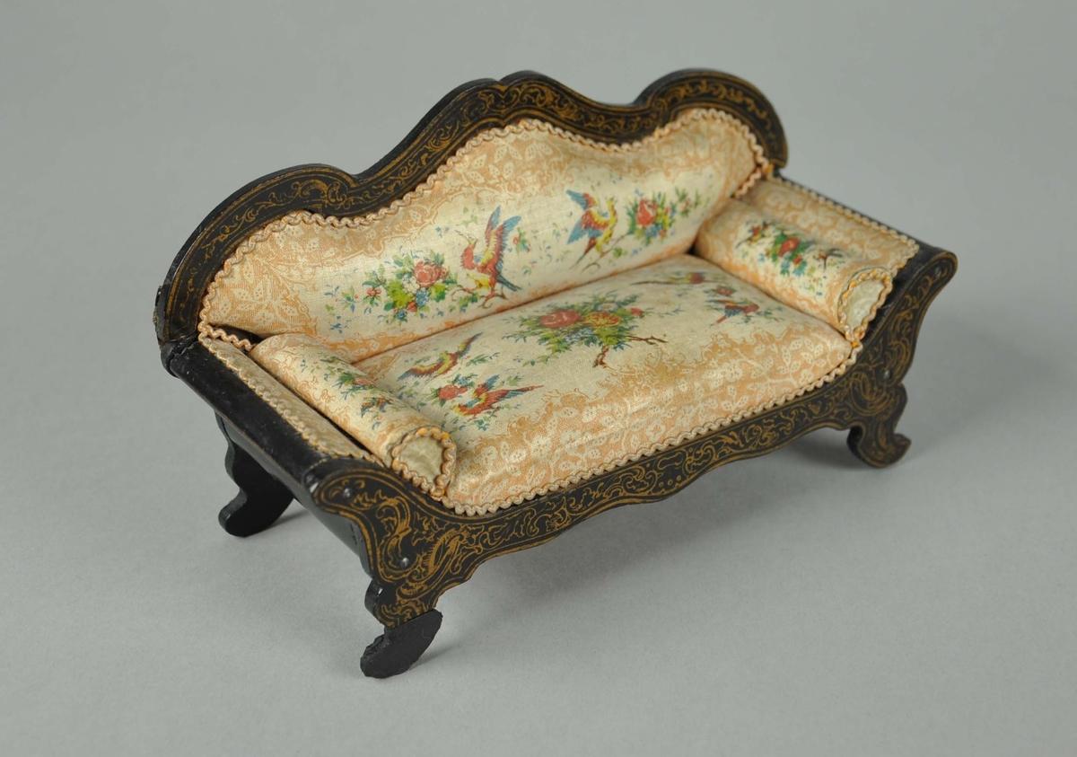 11 møbler til dokkehus. Møblene har stilen nyrokokko. Består av en sofa, fotskammel, 6 stoler, bord, skrivebord og konsollspeil. Stoler, sofa, bord, skrivebord og konsollspeil er laget av treverk med malt dekor i gullfarge. Stoler, sofa og fotskammel har puter med flerfarget dekor av blomster og fugler.Konsollspeilet er satt sammen av to deler.