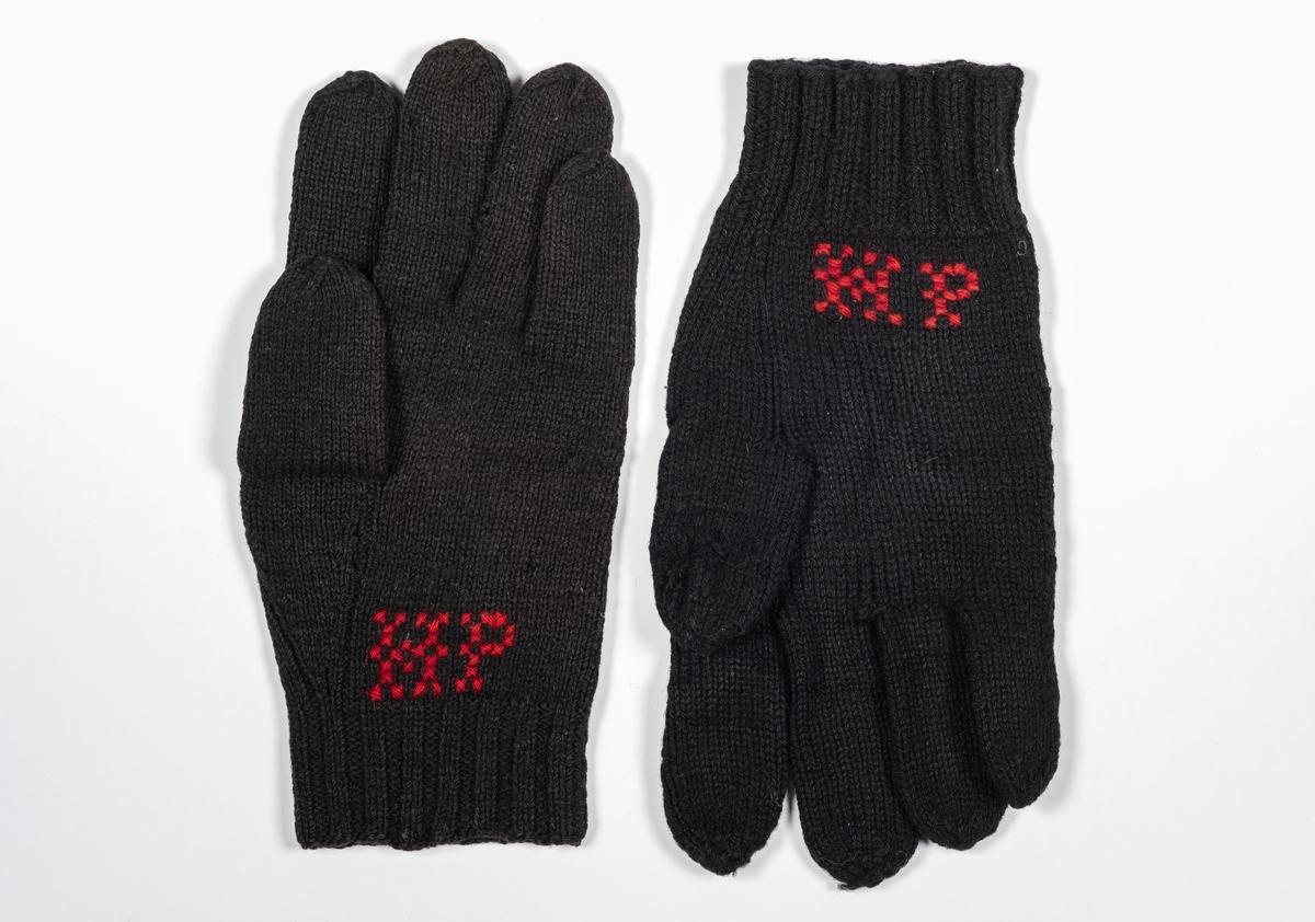 Ett par svarte strikkede hansker med broderte initialer.