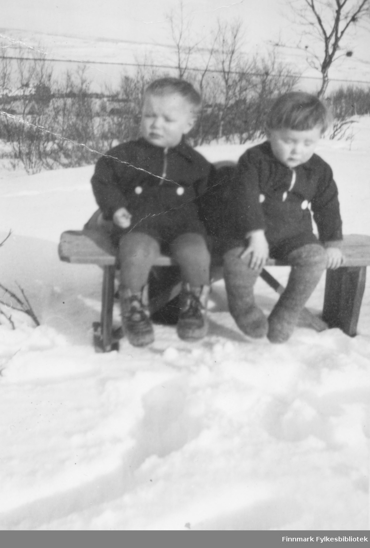 To smågutter fotografert på en benk en vinterdag. De er Odd Iversen og Matti Hedmund Iversen. Stedet er ukjent, men kan være Barsnes i Nesseby kommune.