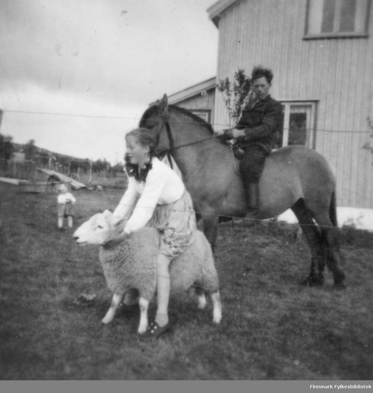 Anna Agnethe Mathisen rir på en sau og farbroren Nils Mathisen rir på en hest. Et ukjent barn står litt i bakgrunnen.