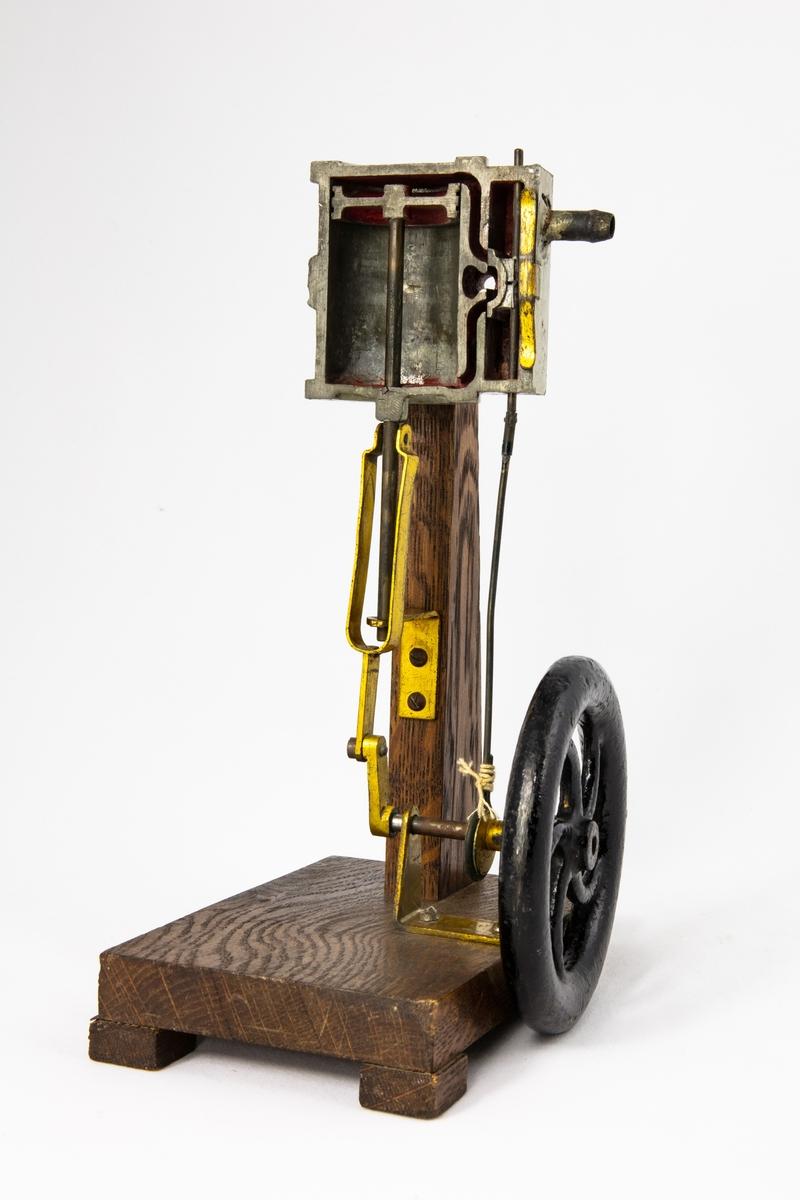 Ångmaskin, modell, på bottenplatta i trä.   En genomskärning av mekaniken i en ångmaskin. Ånga pressas in genom ett rör och konstruktionen får pistongen i cylindern att pressas upp och ned och får axeln att röra sig.  Undervisningsmaterial från skolor i Vänersborg.