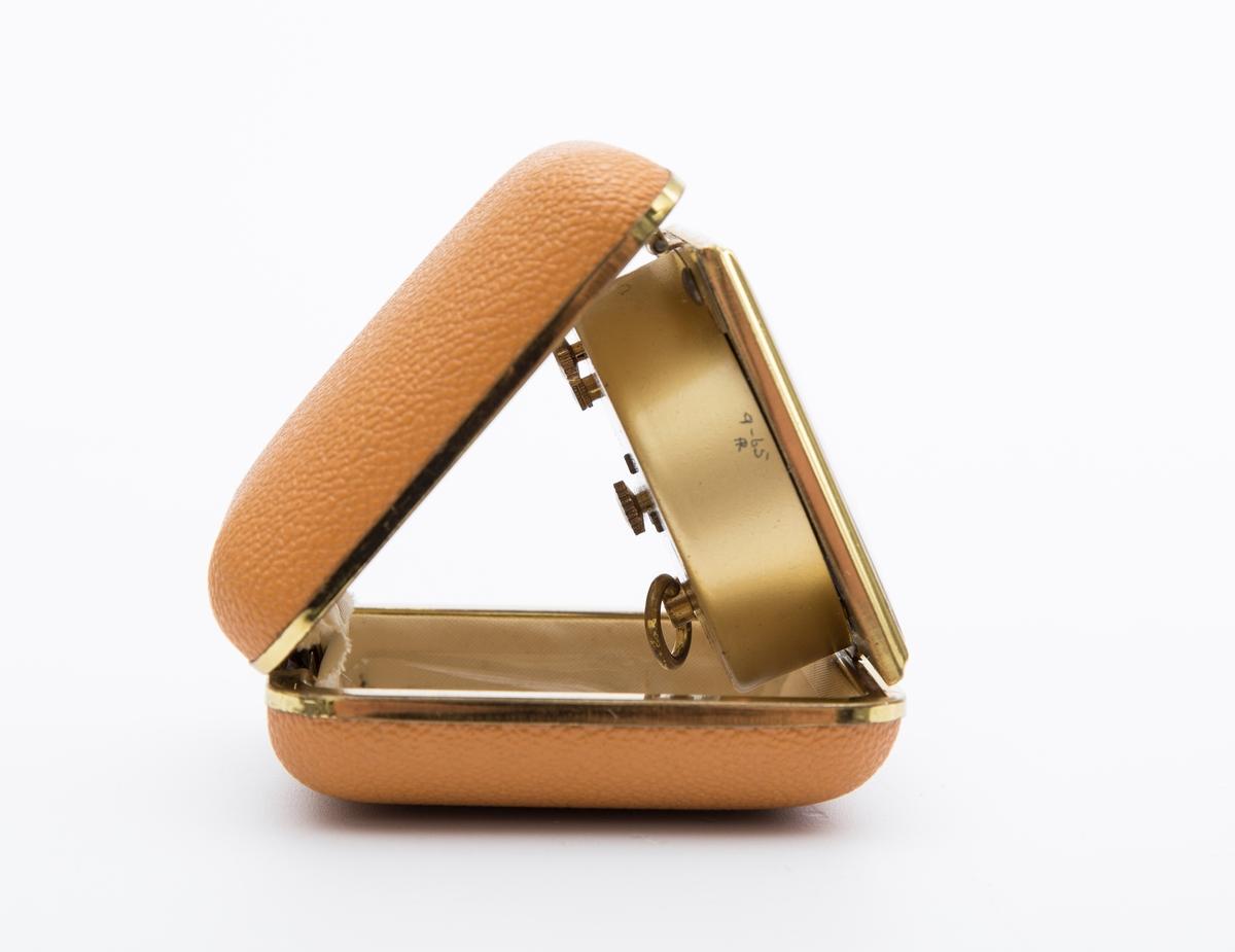 """Klokke, vekkeklokke, reiseklokke, i lys brunt hard plast, gullfarget metall og for i kremhvit, syntetisk stoff. Firkantet boks med avrundete kanter. Urskive hvit, like tall og visere i gullfarget metall. Mrk på urskive:""""Europa - 2 Jewels"""". Innripet i metall:""""9-65"""" og """"FR"""" eller """"AR"""". Fabrikkprodusert."""