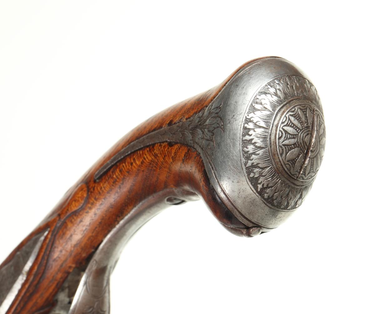 Slaglåspistol omändrad från flintlås. Den har helstock med några få utskärningar. Kolvkappa, sidobleck, låsbleck, rörkor, hane och varbygel samt pipa tillverkade i polerat stål försett med ciselerade blomsterdetaljer. Pipan har även inläggningar i mässing baktill samt runt kornet. Pistolen har ett filat gropsikte, och det finns ett korn av mässing. Mynningsblecket samt stötändan på laddstocken har hornbeslag. Pipan är slätborrad med en innerdiameter på 14 mm.  Inskrivet i huvudkatalog 1890.