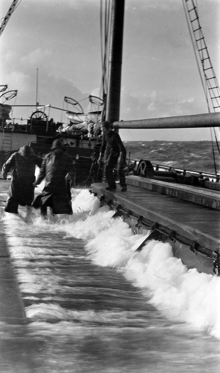 Arbeid på dekk på D/S STORFOND. Bølger slår over dekk. To av mannskapet i oljehyrer.