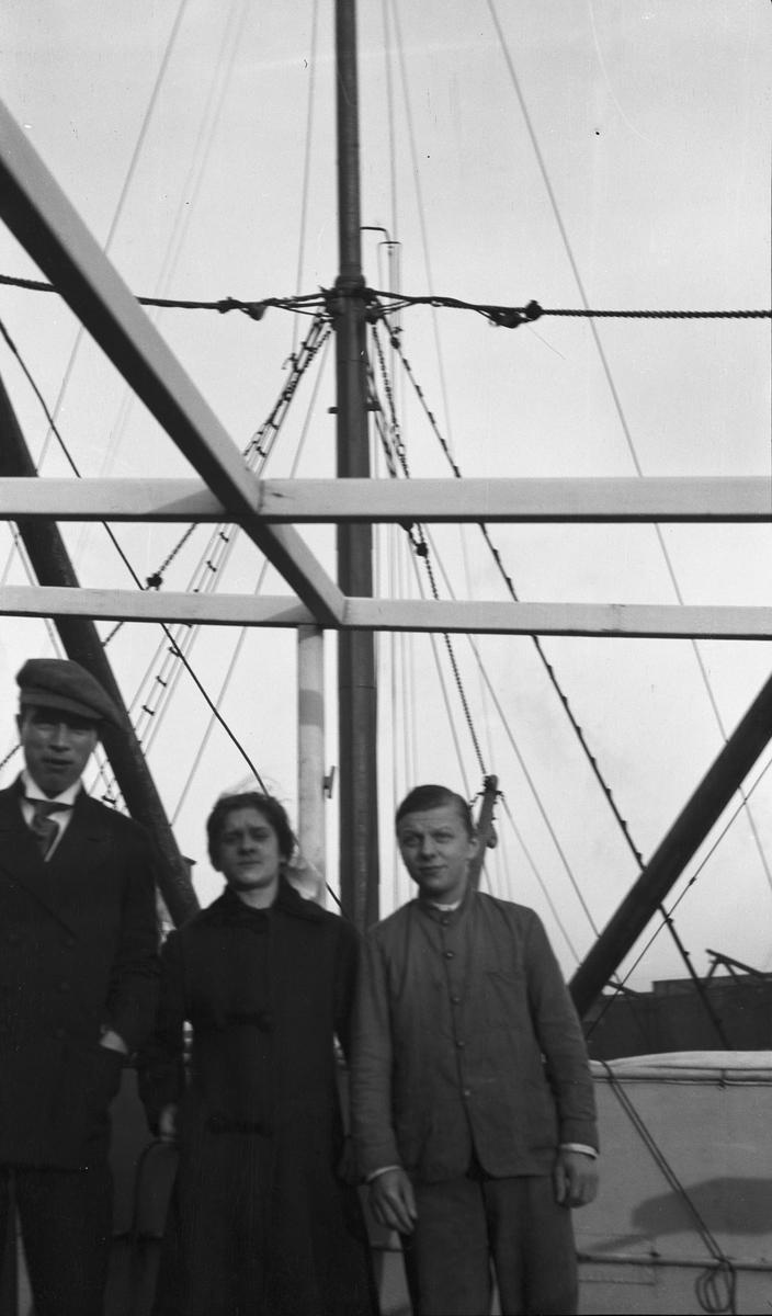 To menn og en kvinne på dekk om bord på DS STORFOND.