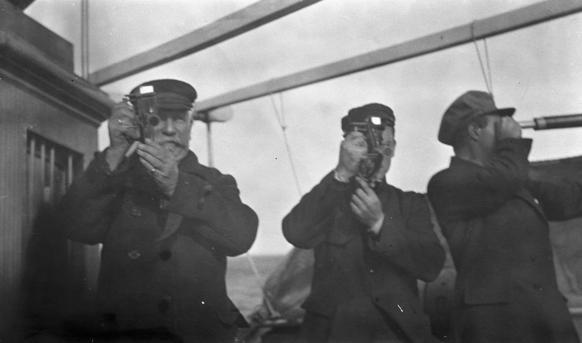 Kaptein Waage og en annen mann tar ut kurs med sekstant. En tredje mann speider i en langkikkert. Om bord på DS STORFOND.