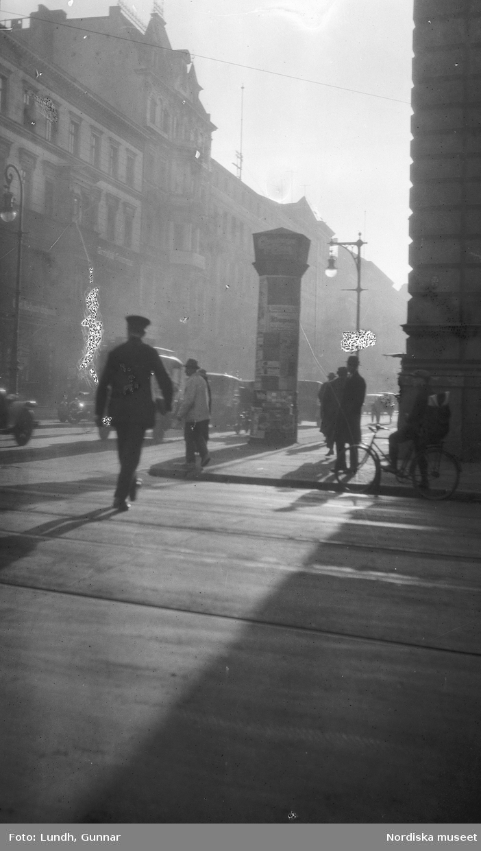 """Motiv: Utlandet, Berlin 114 - 146 ; Gatuvy med kvinnor och män som går på en trottoar, anteckningar på kontaktkarta 126 """"Siegessäule monumentet"""" 128 """"Leipziger strasse""""."""