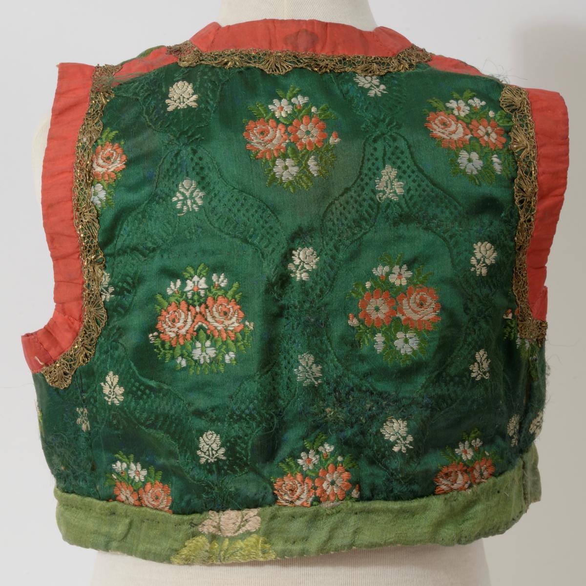 Grønn bunn, blomster i rødt, grønt, hvitt. åpning foran, kantet m. rødt silkebånd, gullknipling, 3 sett maljer, snor m. sølvspisser, gravert L.F. 830.