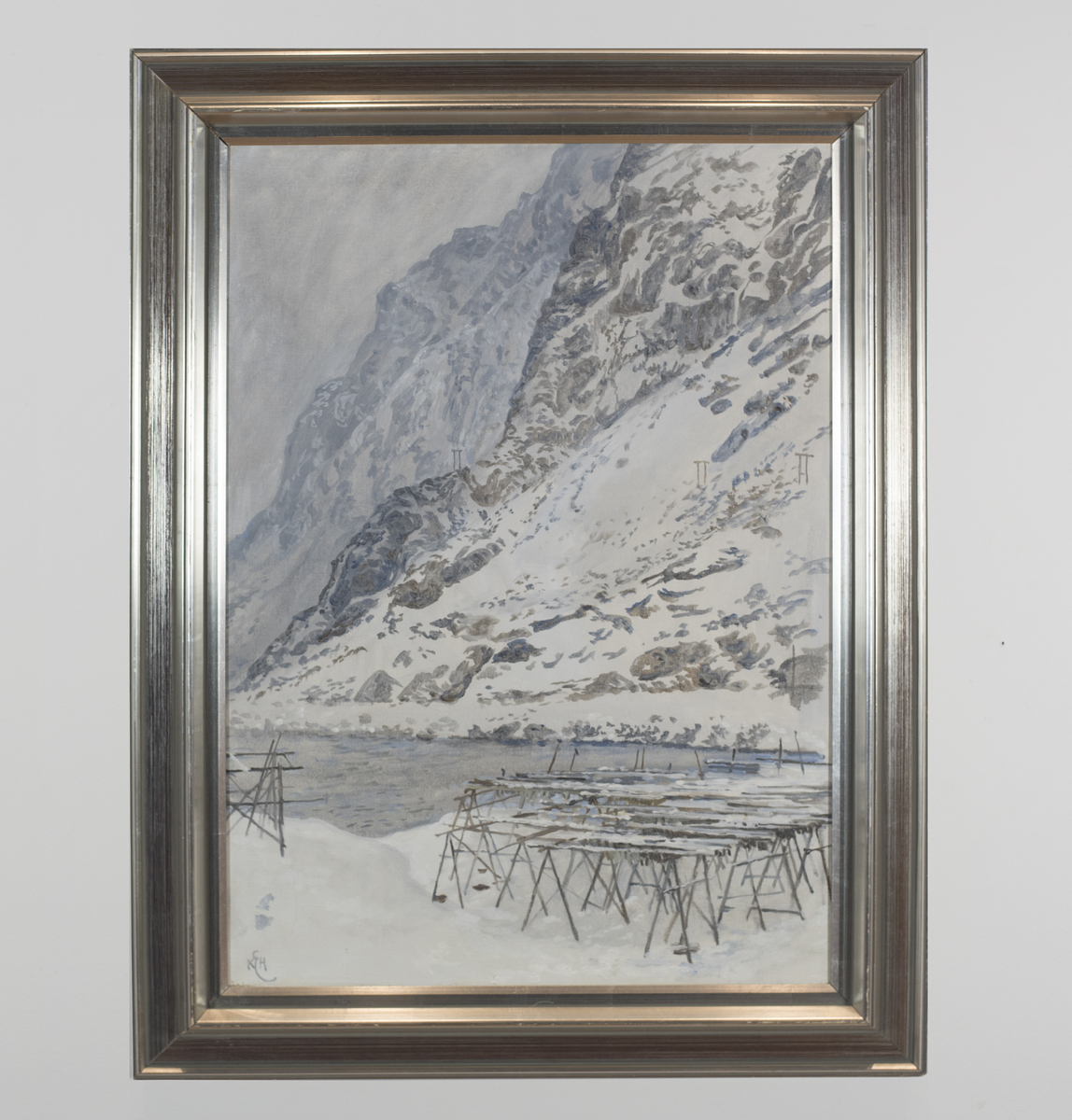 Vinterlig landskap med bratte fjellsider og hav. Fiskehjell sees i forgrunnen.